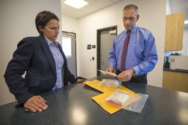 """Arlington Police Chief Fred Ryan, right, and inspector Gina Bassett review toxicology reports on cocaine evidence, looking for the possibility of fentanyl. """"Law enforcement tells us that the next wave of the addiction crisis is fentanyl-laced cocaine,"""" Ryan says. (Jesse Costa/WBUR)"""