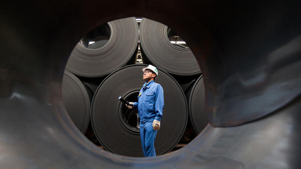 A quality control engineer examines hot-rolled coils of steel being stored in 2015 at South Korean manufacturer POSCO's facility.
