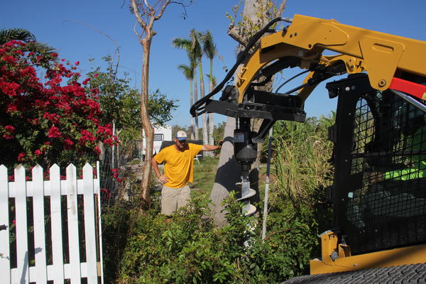 Patrick Garvey helps a landscaping crew drill holes for a new fence at Grimal Grove on Big Pine Key.