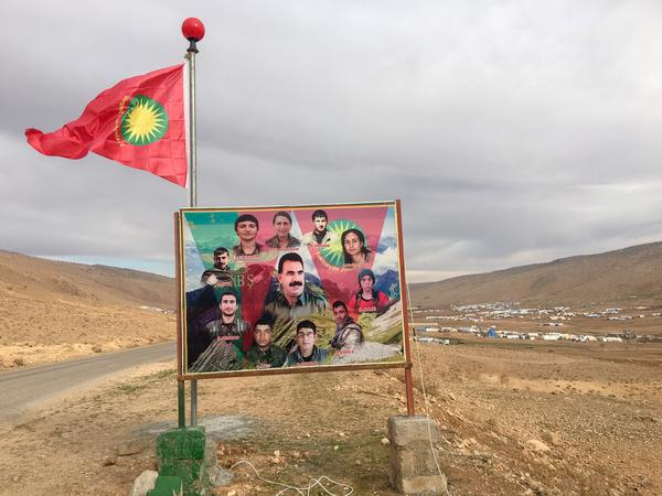 A flag of the Yazidis' Sinjar Resistance Units and photos of fighters killed battling ISIS on the side of the road in Sinjar, in northern Iraq. The pictures show slain fighters from both the resistance units and a Turkish Kurdish guerrilla group that backs them.