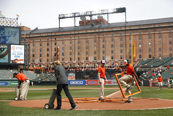 Groundskeepers prepare the infield before an opening-day baseball game between the Minnesota Twins and the Baltimore Orioles on Thursday in Baltimore.