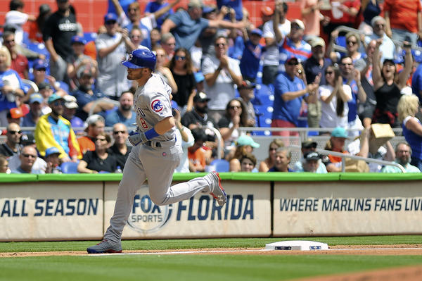 Chicago Cubs center fielder Ian Happ rounds third base after hitting a home run in the first inning of a baseball game against the Miami Marlins on opening day.