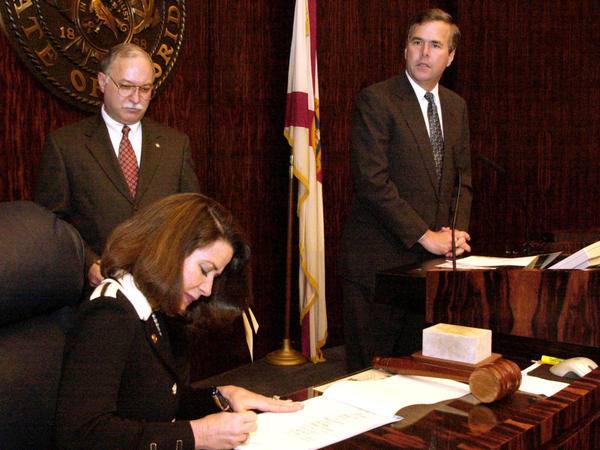Florida Secretary of State Katherine Harris signs the final certification of the state's electoral votes to Republican George W. Bush on Dec. 18, 2000, in Tallahassee.