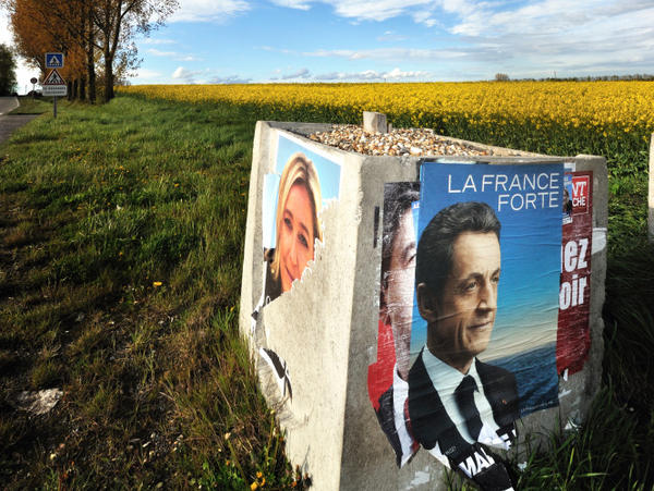 A campaign poster for French President Nicolas Sarkozy stands next to a torn poster of National Front candidate Marine Le Pen in northern France. Sarkozy needs Le Pen's far-right voters if he is to win the runoff election on Sunday.