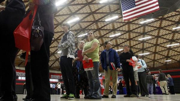 People wait in a line at a job fair on April 10, 2012, in Gresham, Ore. Employment grew by 115,000 last month, but the unemployment rate dip was likely due to people leaving the workforce rather than people getting hired, analysts say.