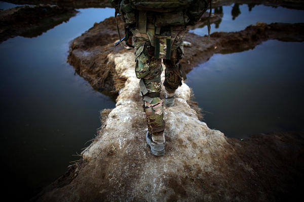 "An American soldier walks between puddles while on patrol. U.S. troops based at a combat outpost in the village of Zangabad have nicknamed it ""Zangaboom,"" because roadside bombs are a constant danger."
