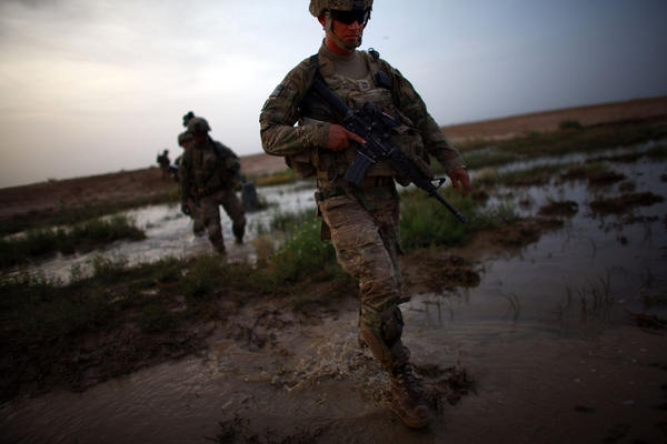 Sgt. Matthew McMurray walks through a flooded riverbed while on a joint operation.
