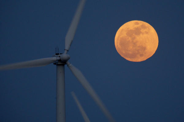 A supermoon rises behind wind turbines Saturday near Palm Springs, Calif.
