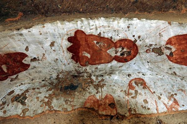 Damaged paintings at the top of the cave's entrance are shown in 2008.
