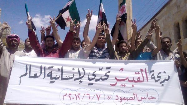"Anti-government protesters in the northern Syrian village of Hass protest on Thursday following the deaths of dozens of civilians a day earlier in the village of Mazraat al-Qubair. The banner reads, ""The al-Qubair massacre challenges the world's humanity."""