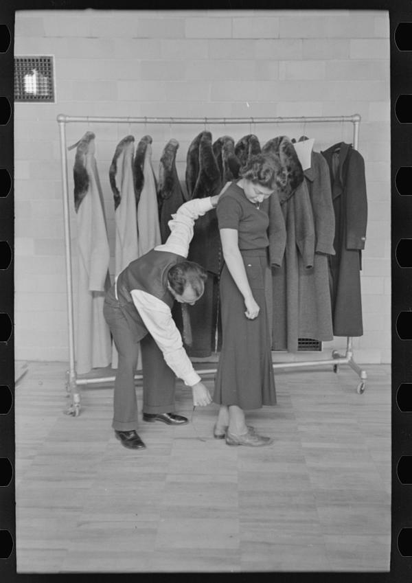 A tailor measures a woman for a coat, which was produced by the town's garment factory.