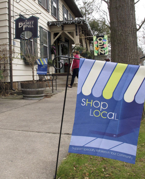A flag urges customers to shop locally near a store in Boalsburg, Pa., on Friday. Owners of small stores hope to get a boost from Small Business Saturday.