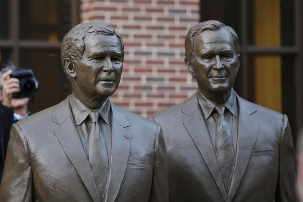 Statues of former presidents George W. Bush (left) and his father, George H.W. Bush, greet visitors to the George W. Bush Presidential Library in Dallas.