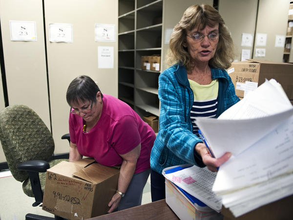 Document prep technician Carol Sine (left) and tracer Debra Barrett process firearm transaction documents at the National Tracing Center in Martinsburg, W.Va.