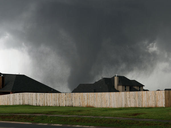 A tornado moves past homes in Moore, Okla. on Monday.