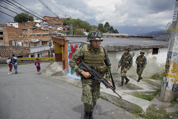 Colombian army soldiers patrol Medellin's Loma de Cristobal neighborhood after warring gangs forced dozens of families to flee. Medellin used to be the most dangerous city in the world, but officials embarked on innovative projects designed to make life better in tough neighborhoods.