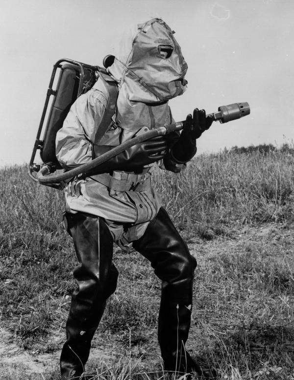 A U.S. Marine carries a light flame-thrower while wearing experimental clothing designed to protect against atomic, biological and chemical warfare in 1960.