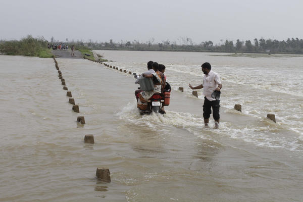 A family crosses a flooded road as they return to their village near Gopalpur, Orissa state.