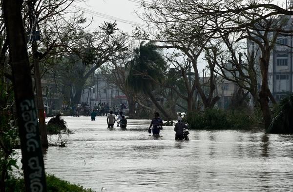 Residents walk through floodwaters Sunday near where Phailin made landfall in Gopalpur a day earlier. Phailin has been blamed for 17 deaths.