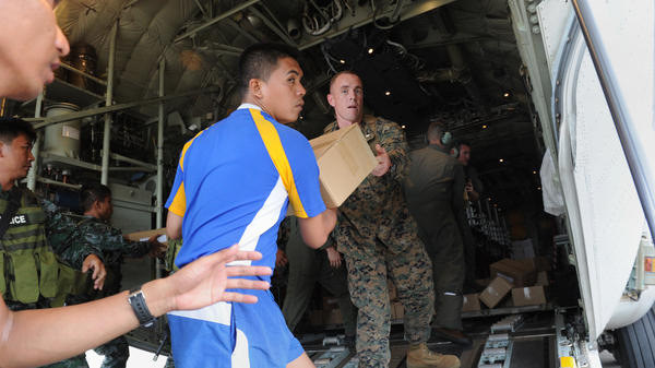 Military personnel from the U.S. and the Philippines unload relief goods at the Tacloban airport, Nov. 11, 2013. Some reports estimate that 10,000 people may have died in the city of Tacloban.