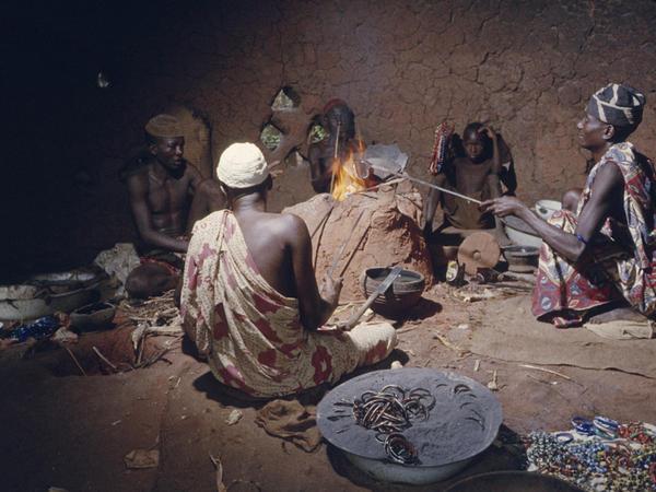 Nupe bead makers around glass-making furnace in 1959, Bida, Nigeria.