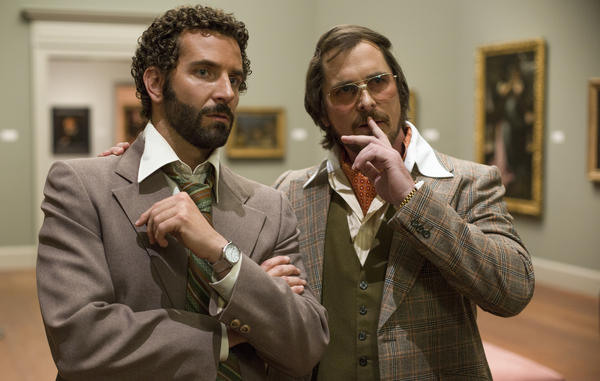 A '70s con artist (Christian Bale, right) is forced to team up with an FBI agent (Bradley Cooper, left) in <em>American Hustle,</em> inspired by a real-life sting targeting corrupt politicians.