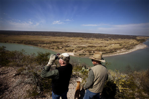 Dob Cunningham (right) and his friend Larry Johnson stand on the edge of Cunningham's 800-acre ranch in Quemado, Texas, which touches the Rio Grande. On the other side, Mexico.
