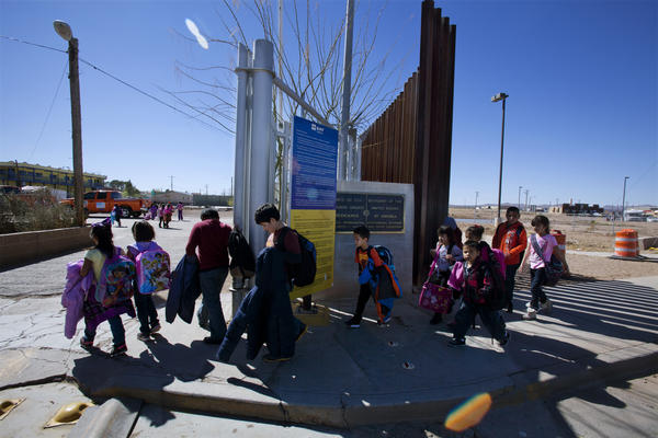 Mayor Skinner lets children off the bus on the New Mexico side of the border (right), where they cross to waiting family members on the Mexico side, in the town of Palomas.