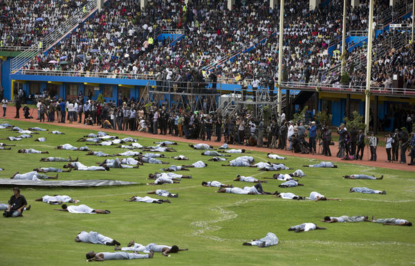 Performers re-enact the events of the genocide at Amahoro stadium on Monday. Ethnic tension between the majority Hutus and minority Tutsis erupted in 100 days of brutality.