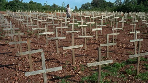 A young Rwandan girl walks through Nyaza cemetery outside Kigali, Rwanda, in 1996, where thousands of victims of the 1994 genocide are buried. The three months of ethnic violence left 800,000, mostly Tutsis, dead.