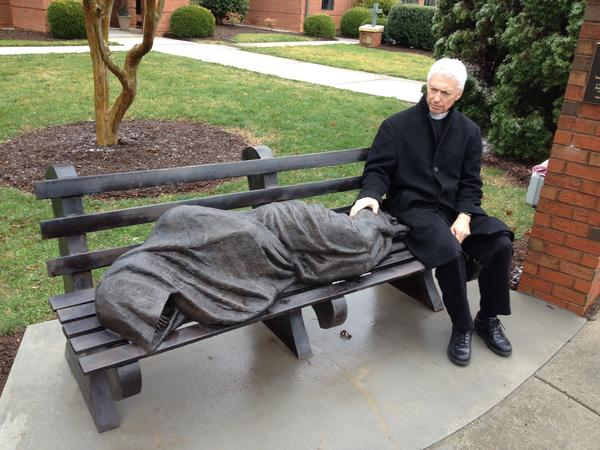 The Rev. David Buck sits next to the <em>Jesus the Homeless</em> statue that was installed in front of his church, St. Alban's Episcopal, in Davidson, N.C.