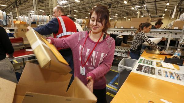 Monica Chavez packs up a box at an Amazon.com fulfillment center Dec. 2, in Phoenix.