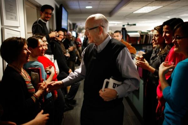 NPR employees line the hallway of the <em>Morning Edition</em> newsroom to cheer for Kasell. He was feted with speeches, champagne and cake following his final 11 a.m. newscast.