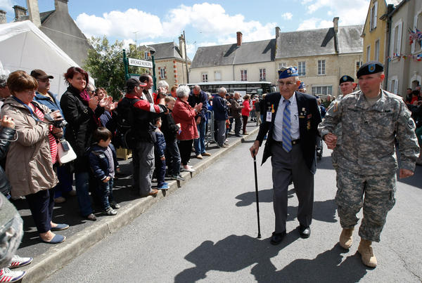 U.S. World War II veteran Arden C. Earll, 89, of Erie, Pa., landed on Omaha Beach on June 6, 1944, with the 29th Infantry Division. A crowd applauds as he arrives at a ceremony in honor of the division Wednesday in La Cambe, France, as part of the commemoration of the 70th D-Day anniversary.