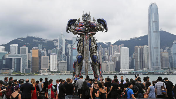 People gather in front of a giant figure of Optimus Prime displayed along the Hong Kong harbor for the world premiere of <em>Transformers: Age of Extinction on </em>June 19.