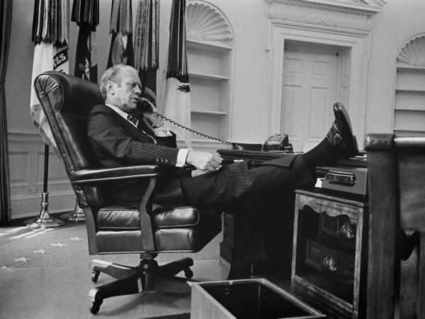 President Ford gets down to business in the Oval Office of the White House, recently emptied of President Nixon's personal effects, on August 12, 1974.
