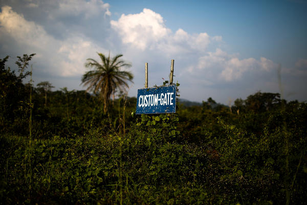 The sign to the customs gate has been nearly overgrown with vegetation. Locals on both sides of the borders are now using the deserted areas near the crossing to plant cassavas and chili peppers.