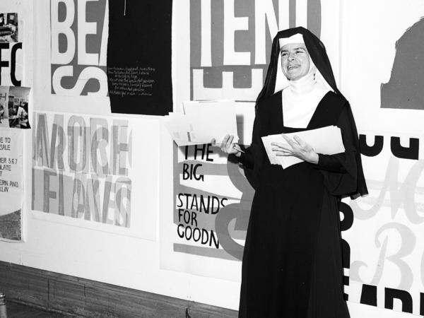 Sister Corita Kent stands in front of her work, including <em>for eleanor</em>, at Immaculate Heart College in 1964.