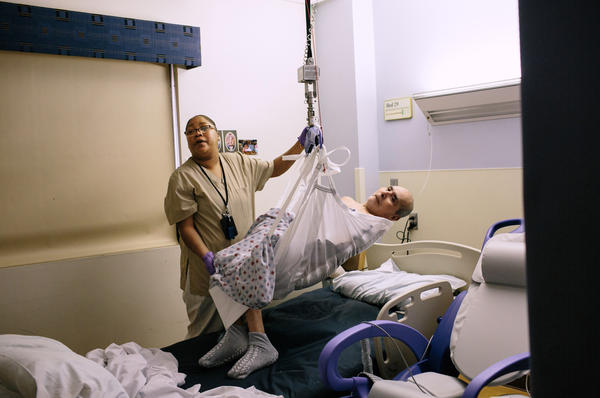 To safely lift Bernard Valencia out of his hospital bed, Cheri Moore uses a ceiling lift and sling. The VA hospital in Loma Linda, Calif., has safe patient handling technology installed throughout its entire facility.