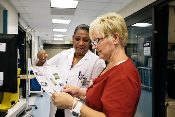 Tony Hilton (left), the safe patient handling and mobility coordinator at the VA hospital in Loma Linda, gives Ruby Baker a safety tip sheet.