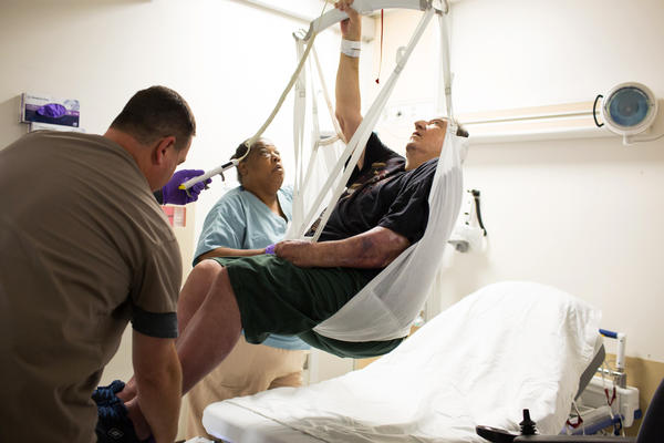 Michael Bolla and Sally Singer lift Leon Anders using a ceiling lift and sling at the VA Hospital in Loma Linda, Calif. The VA system is among a very small number of hospitals that have installed equipment and provided proper training so their nursing staff can avoid physically lifting and moving patients themselves.
