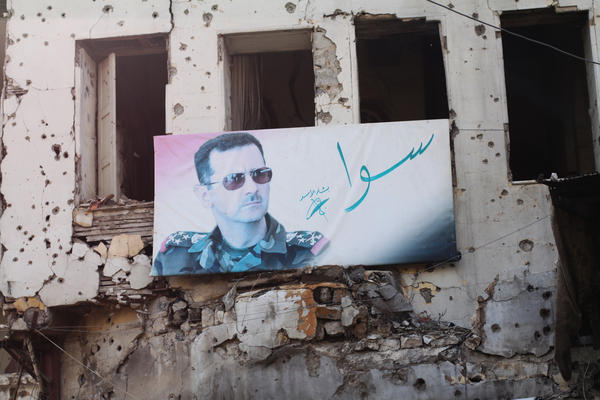 """A portrait of President Bashar Assad hangs in Homs. The slogan reads """"together."""""""