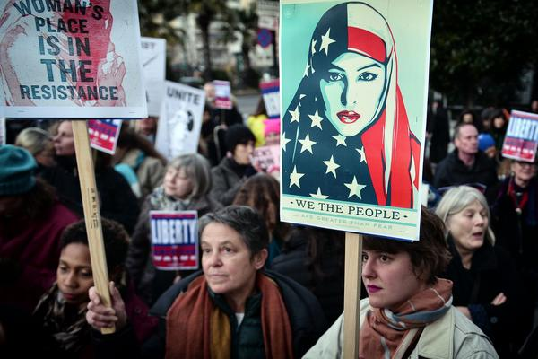 Women hold placards during an demonstration in front of the U.S. embassy in Athens, Greece in solidarity with the Women's March on Washington.