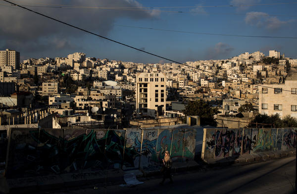 A Palestinian woman walks earlier this month past a concrete barricade on the road that separates an Israeli settlement and a Palestinian neighborhood in Hebron.