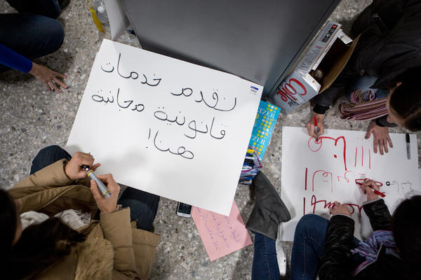 """Volunteers pen signs in Arabic with messages indicating """"free legal help"""" available for arrivals at Washington Dulles International Airport in D.C."""