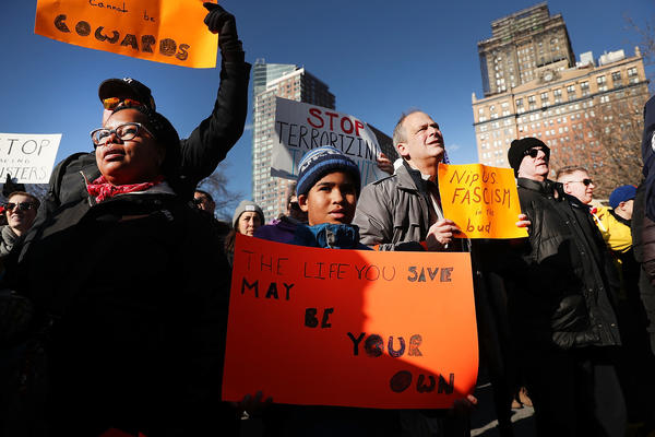People attend an afternoon rally in New York City's Battery Park to protest President Donald Trump's new immigration policies.