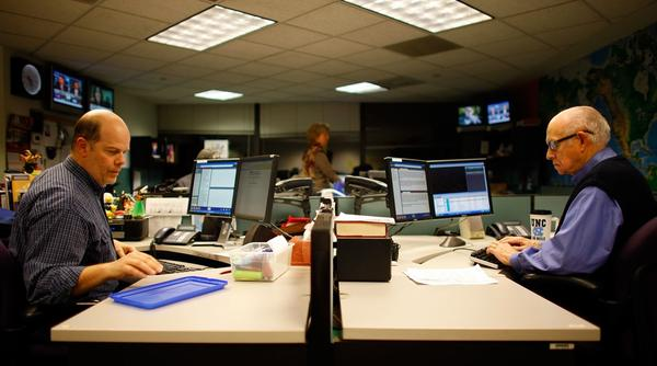Jim Howard (left) edits the newscast, while Kasell works on his scripts in preparation for going on the air, on Dec. 29.