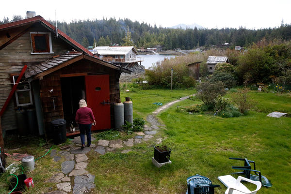 Cassy and the family cat walk across the Peaveys' property in Meyers Chuck, a view of the water in the distance.