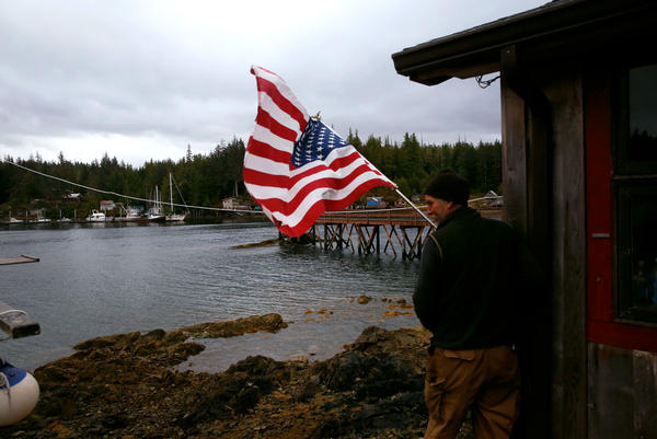 Darrell Lee, 54, puts up the American flag outside the post office — which signals that the mail has arrived in Meyers Chuck.