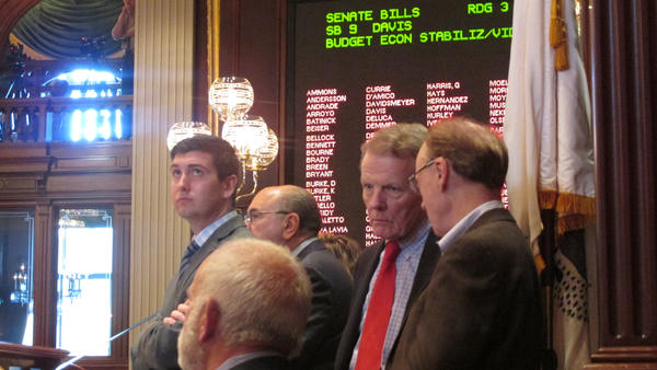 House Speaker Michael Madigan, second from right, confers with aides while watching the end of the debate on legislation to raise Illinois' income tax rate.